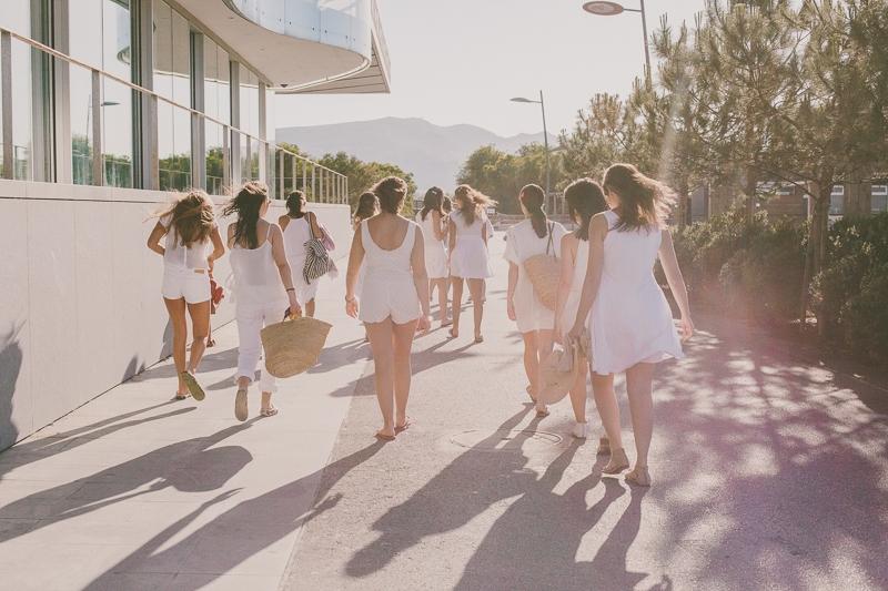 Raparigas vestidas de branco a caminharem para a praia