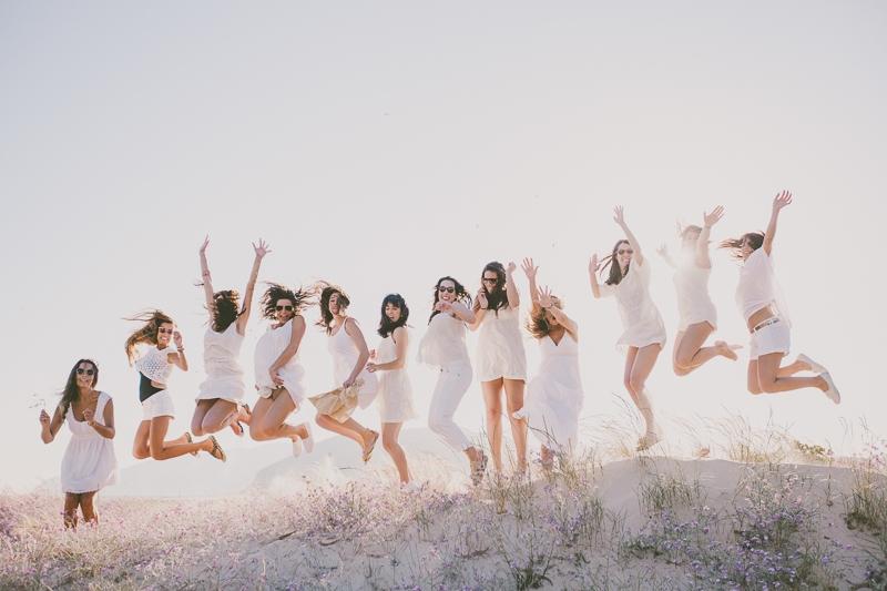Grupo de raparigas vestidas de branco a saltarem na duna
