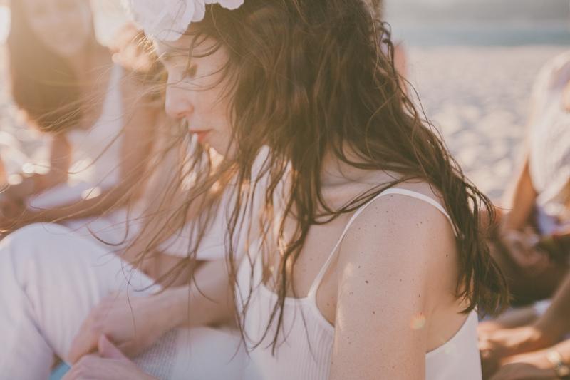 Rapariga vestida de branco na praia com coroa de flores