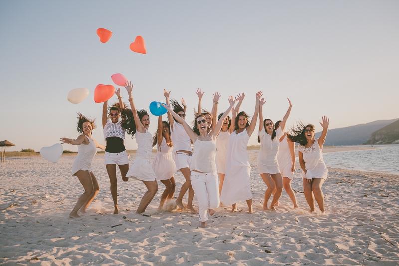 Amigas a saltarem com balões na praia
