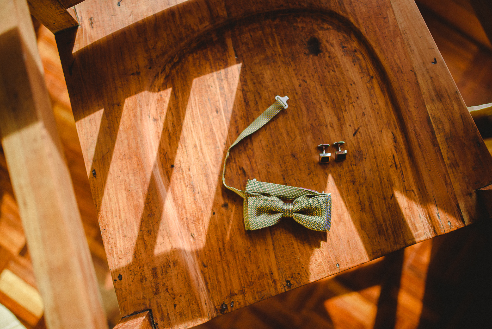 Groom's bowtie displayed on a chair while he gets ready