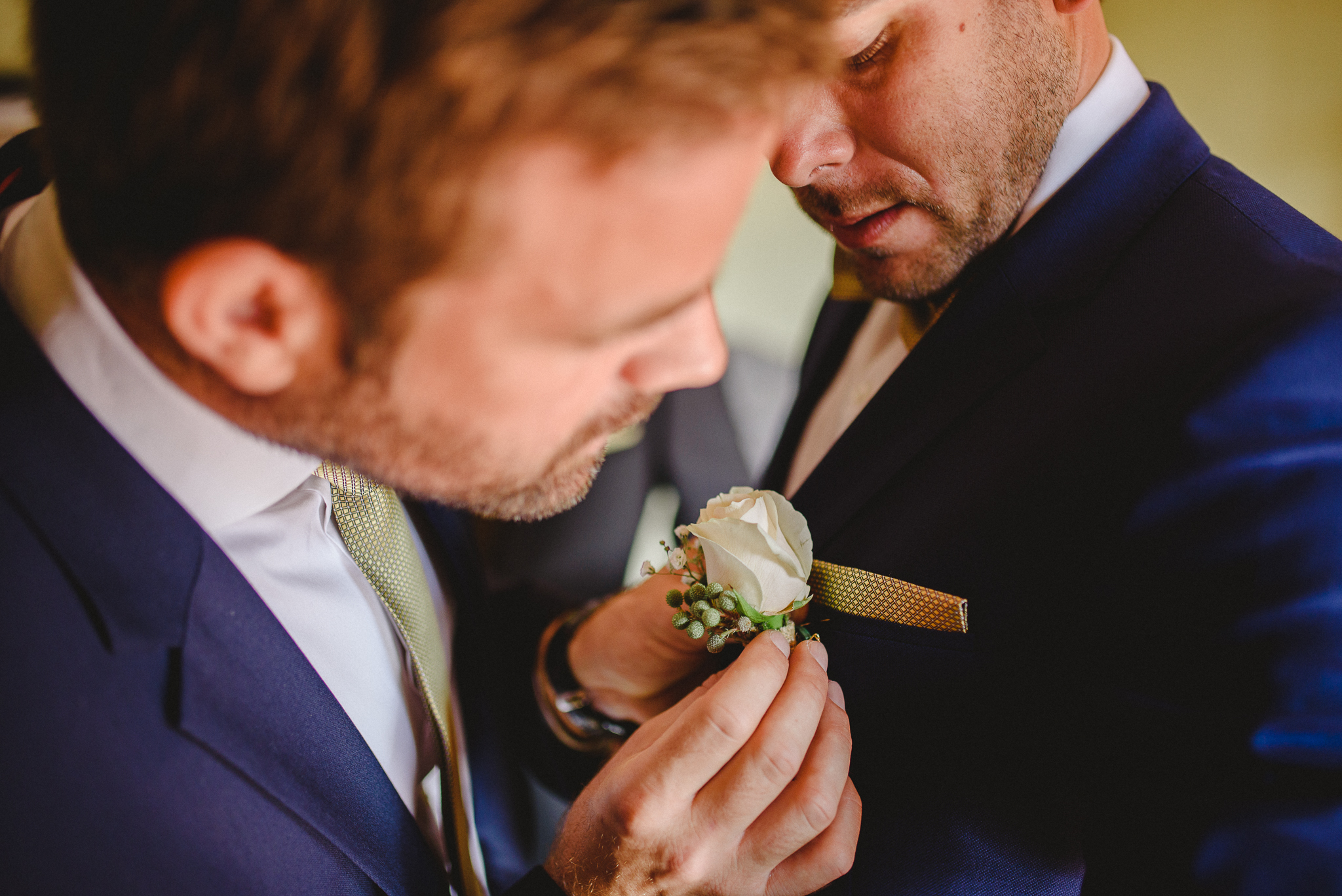 Best man helping groom with his boutonnière.