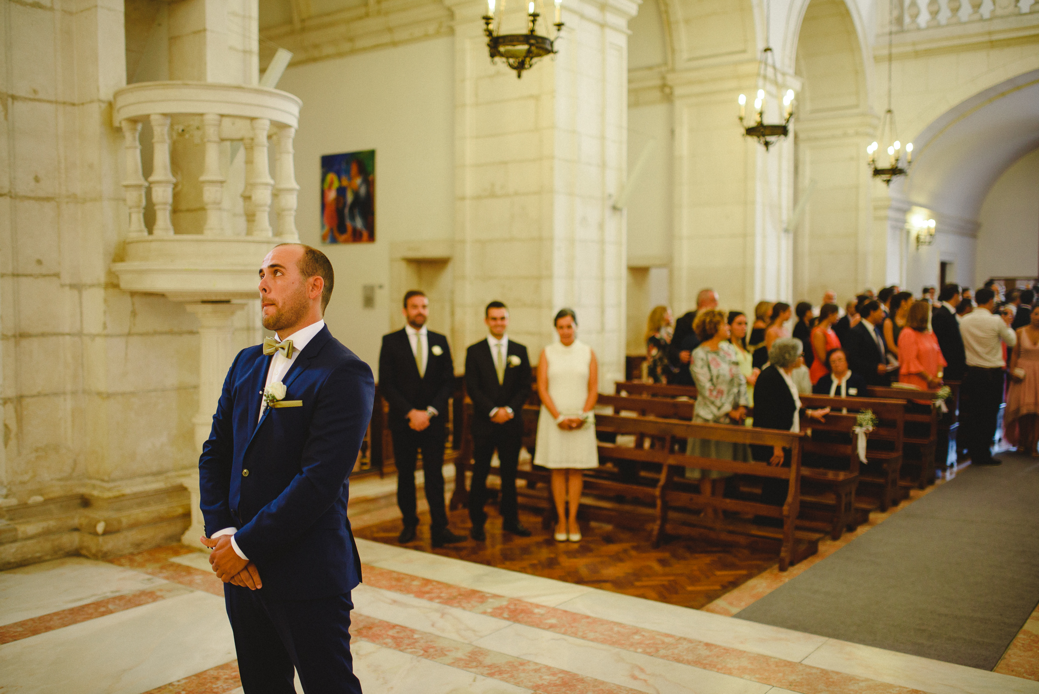 Groom waiting for bride while she walks down the aisle