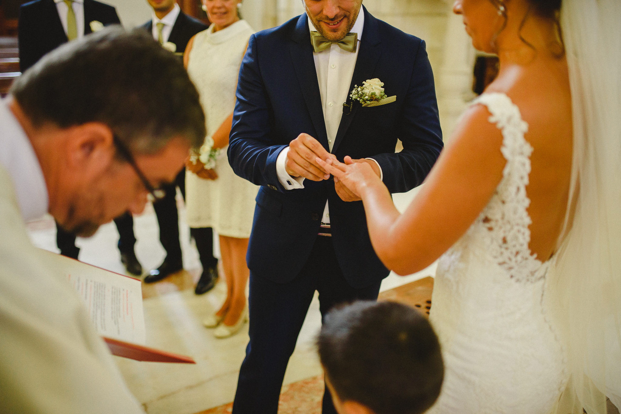 Groom putting wedding ring in bride's finger