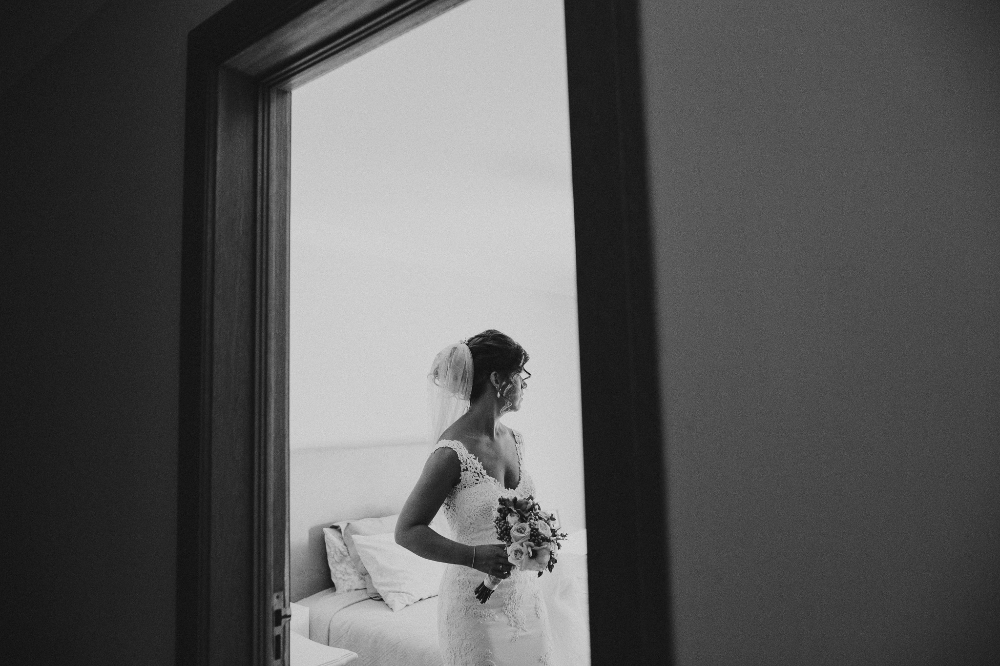 Bride holding her flowers leaving her room.