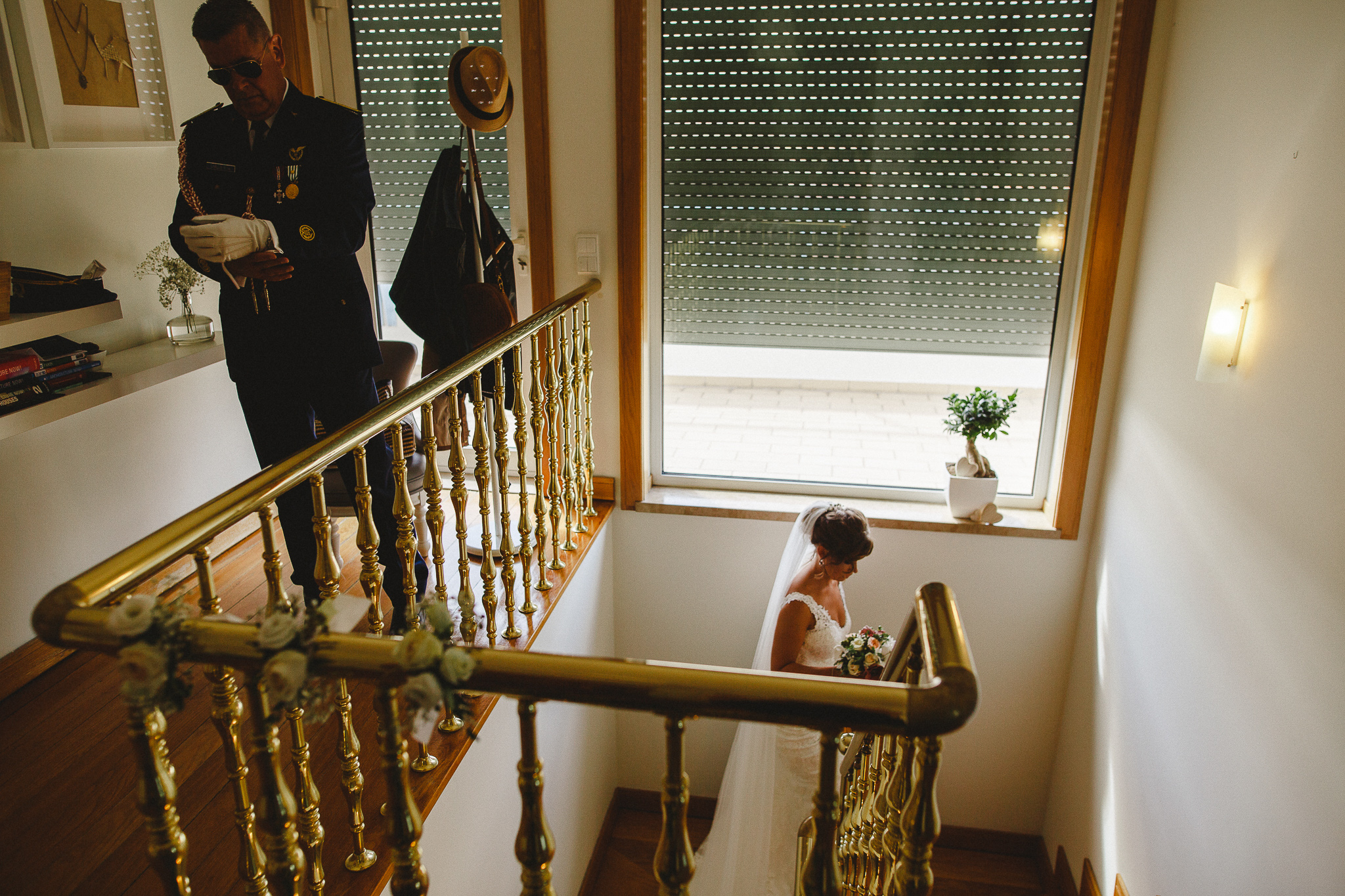 Bride coming upstairs while father of the bride is getting ready to leave the house