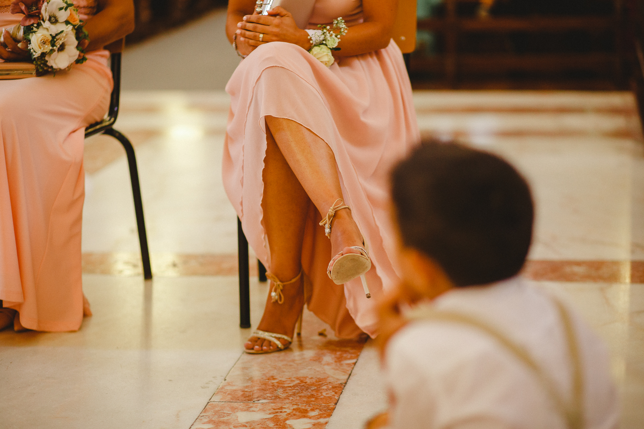 Wedding guest sitting in church in light pink dress and elegant high heels.