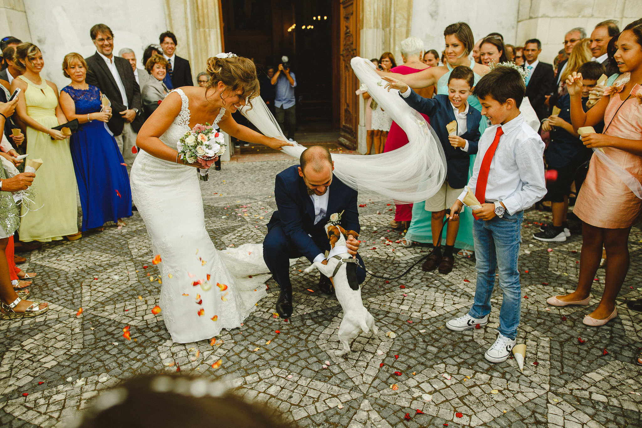 Bride and groom petting their dog after leaving church