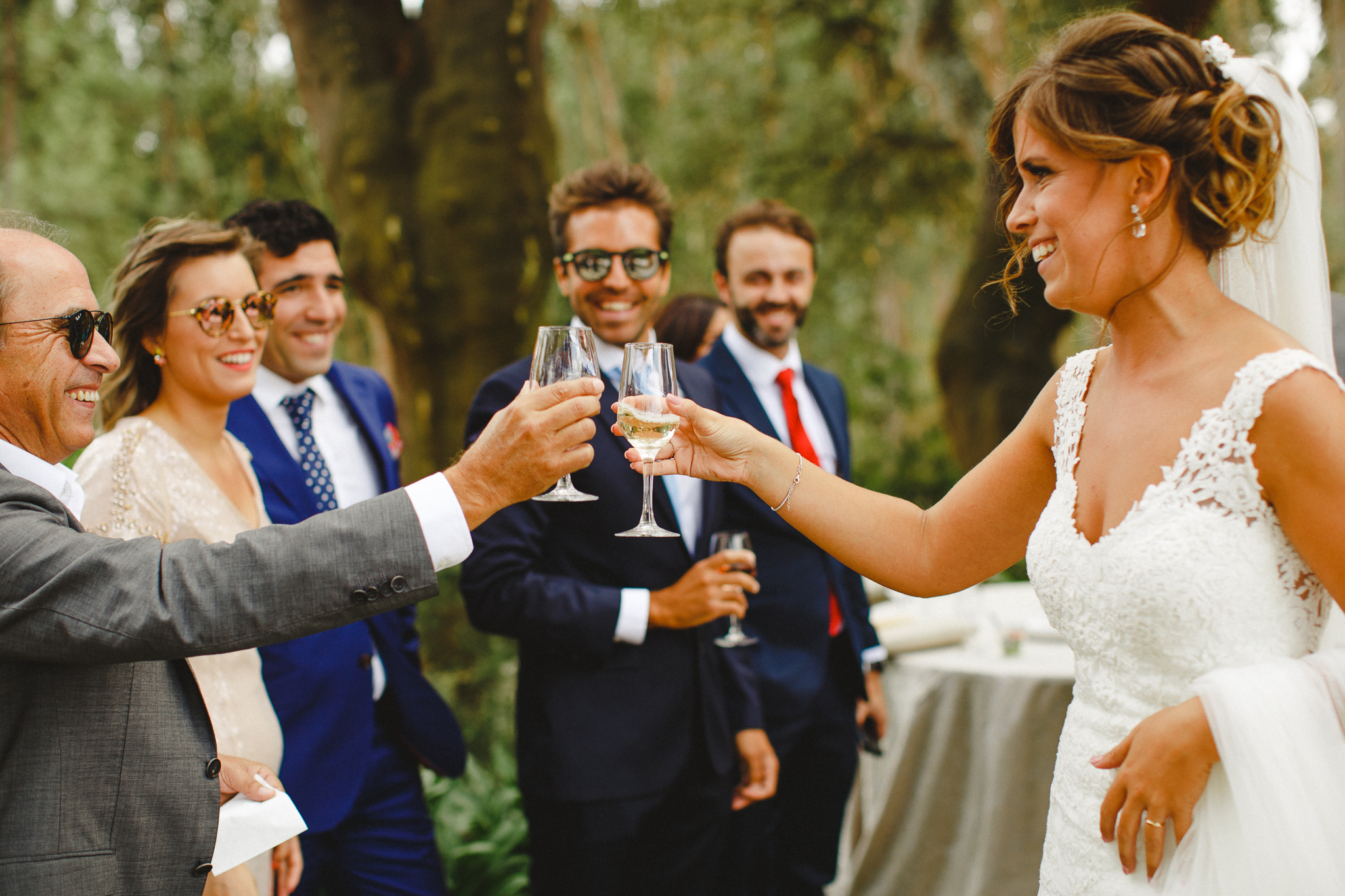 Bride making a toast with friends during cocktail