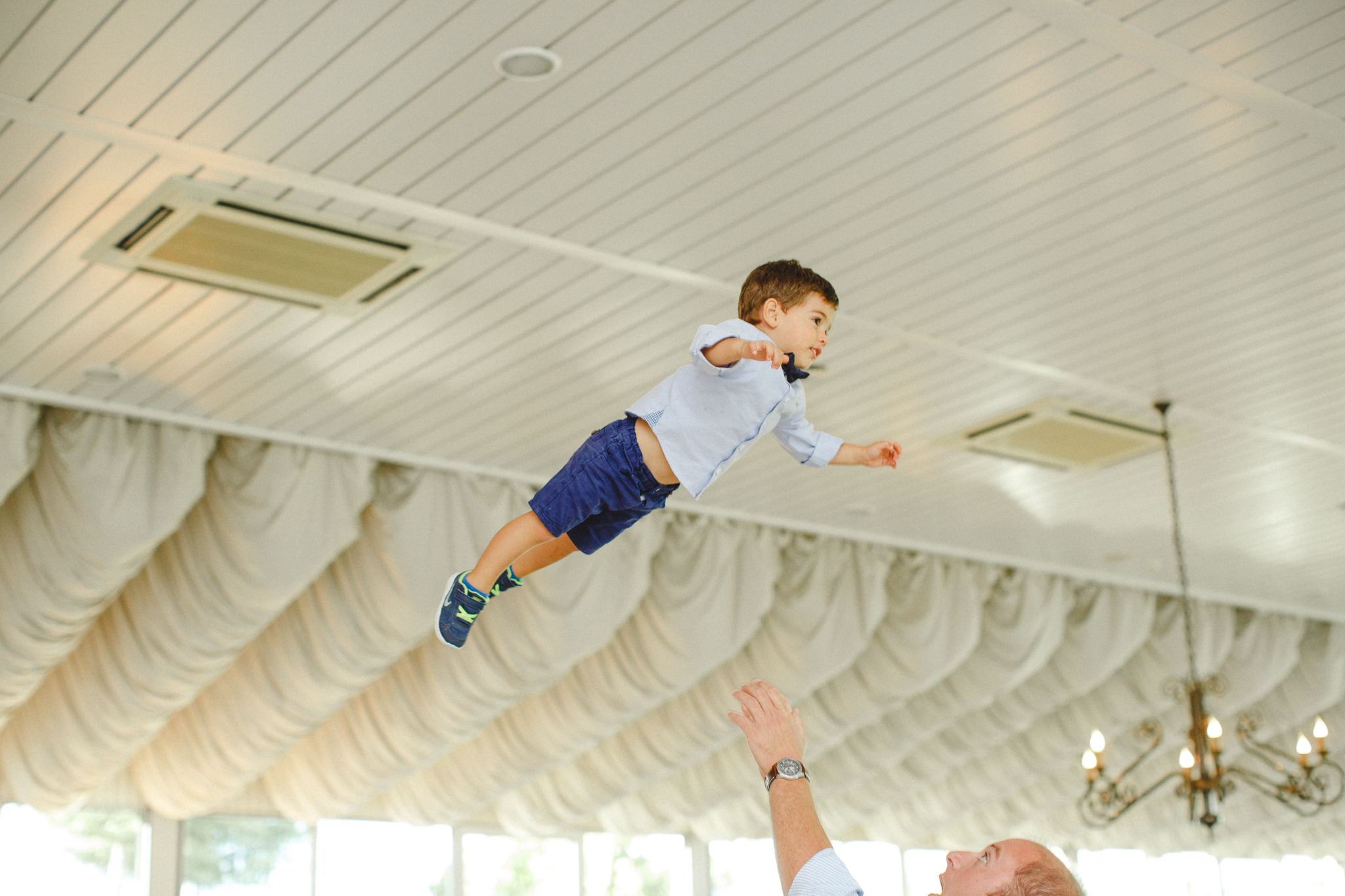 Young kid being thrown up in the air by his father for fun