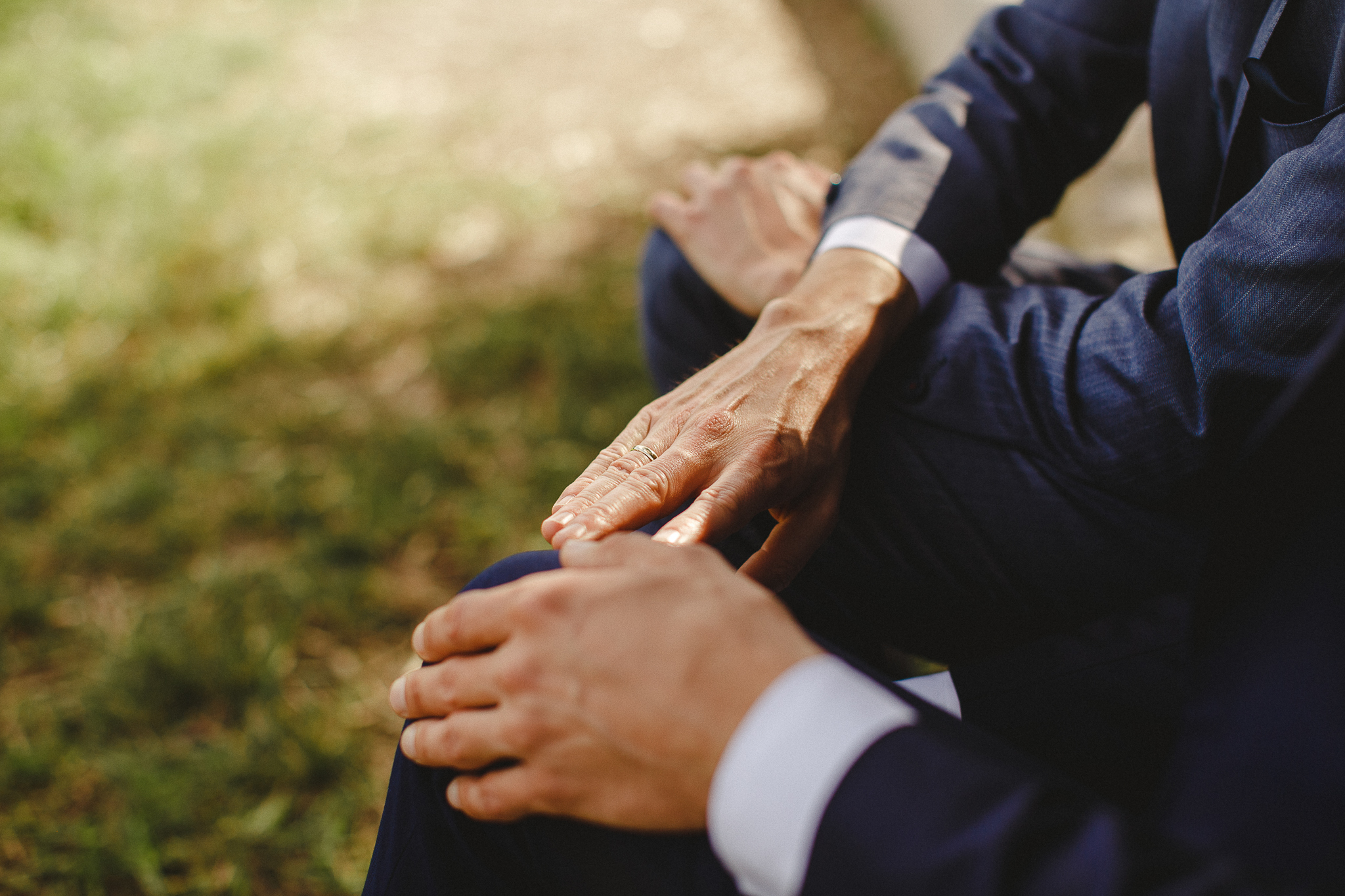 A couple sits under a tree touching hands after their wedding ceremony.