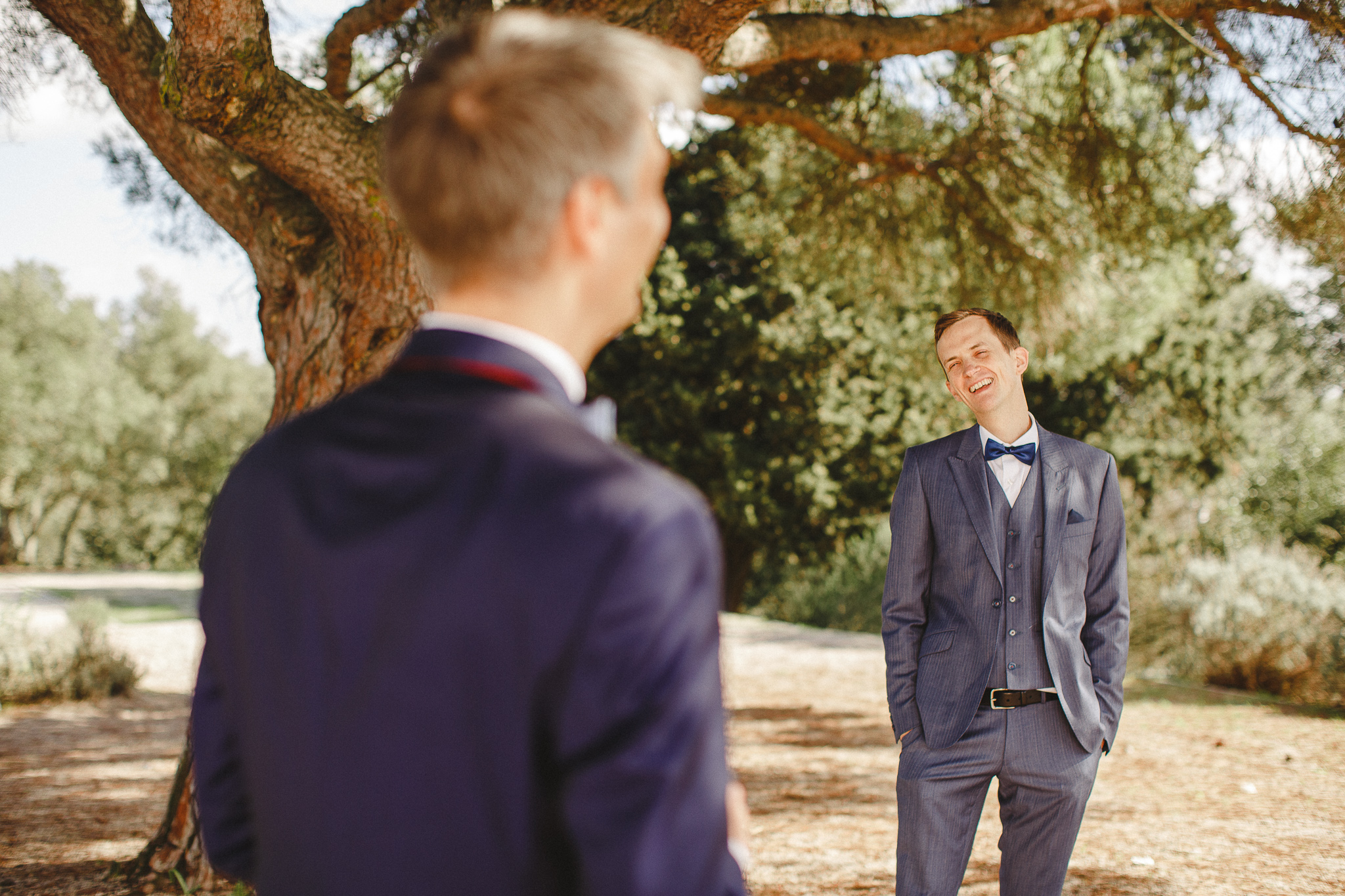 A couple stands under a tree laughing  after their wedding ceremony.