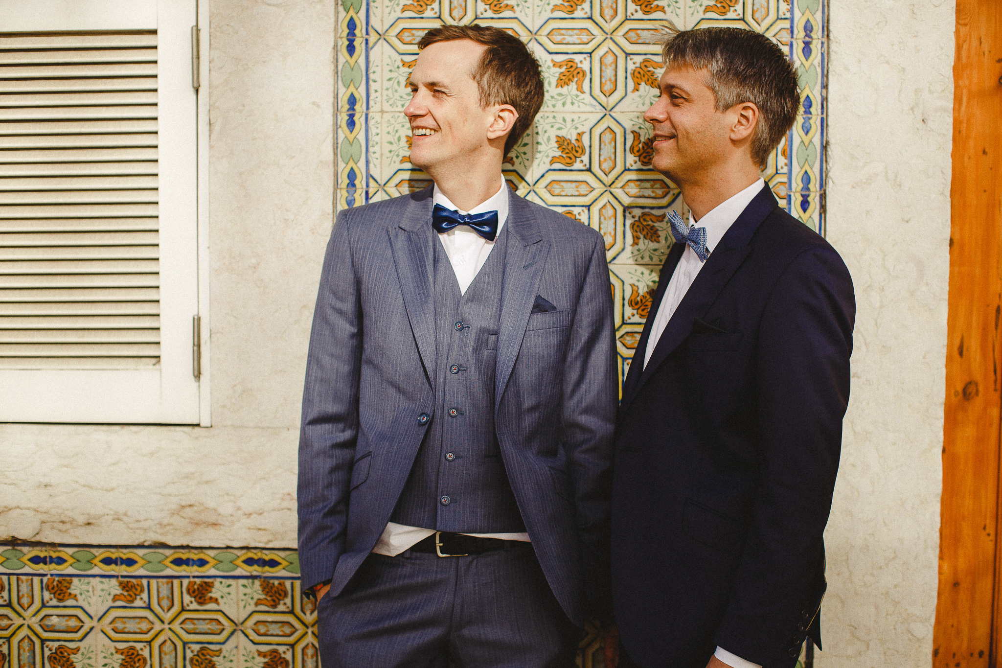 A gay couple stands against a beautiful tile wall in Lisbon after their elopement.