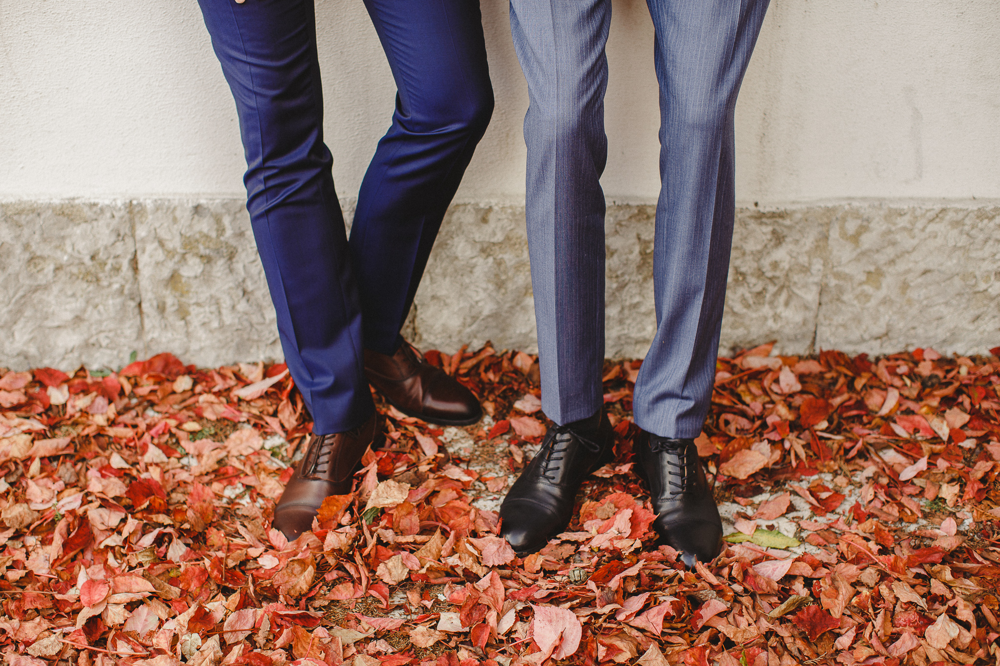Two men stand wearing suits in a ground full of red leaves.