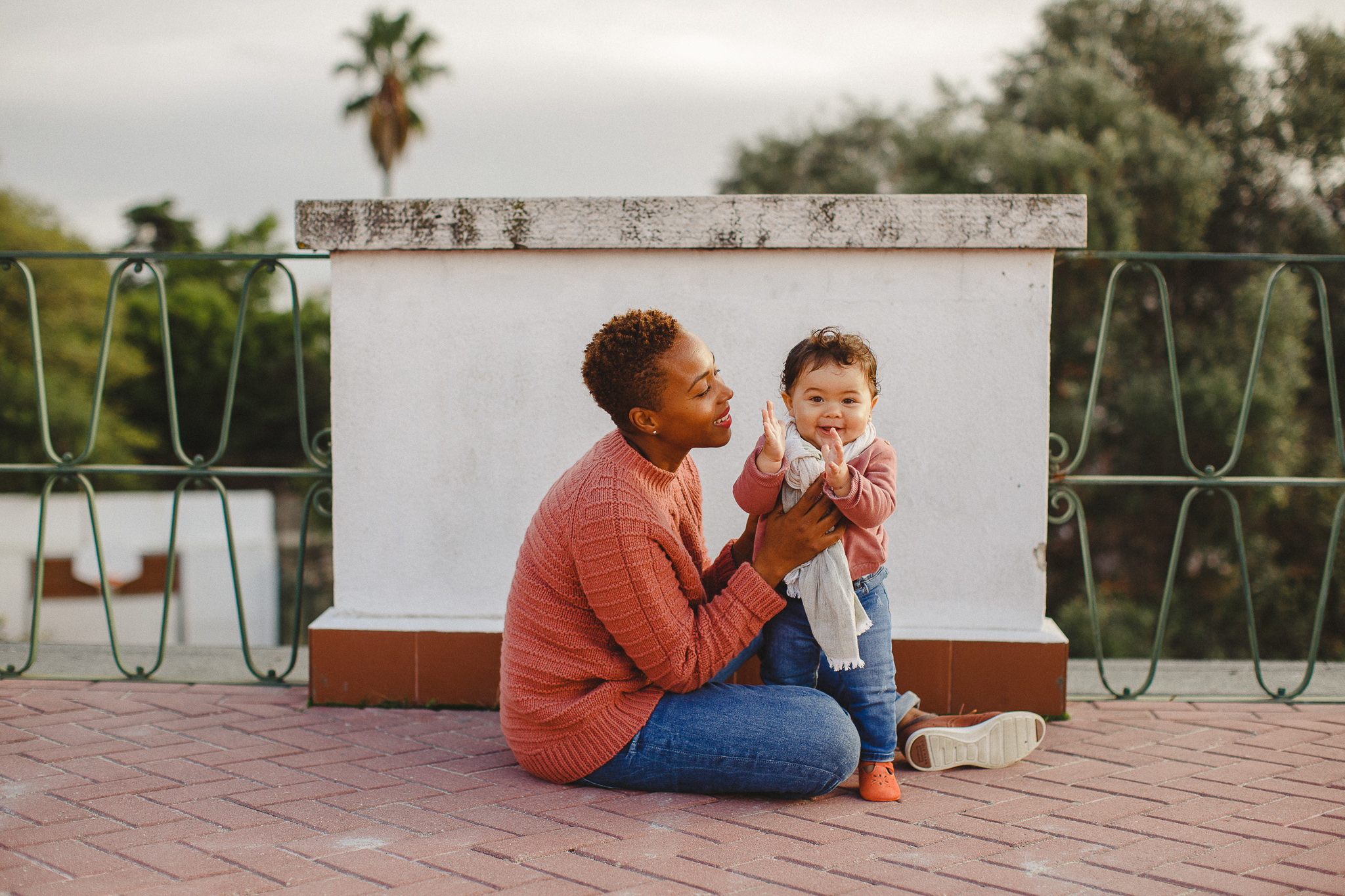 Mom sitting on the ground with baby daughter clapping, during a family photo shoot in Lisbon with Hello Twiggs.