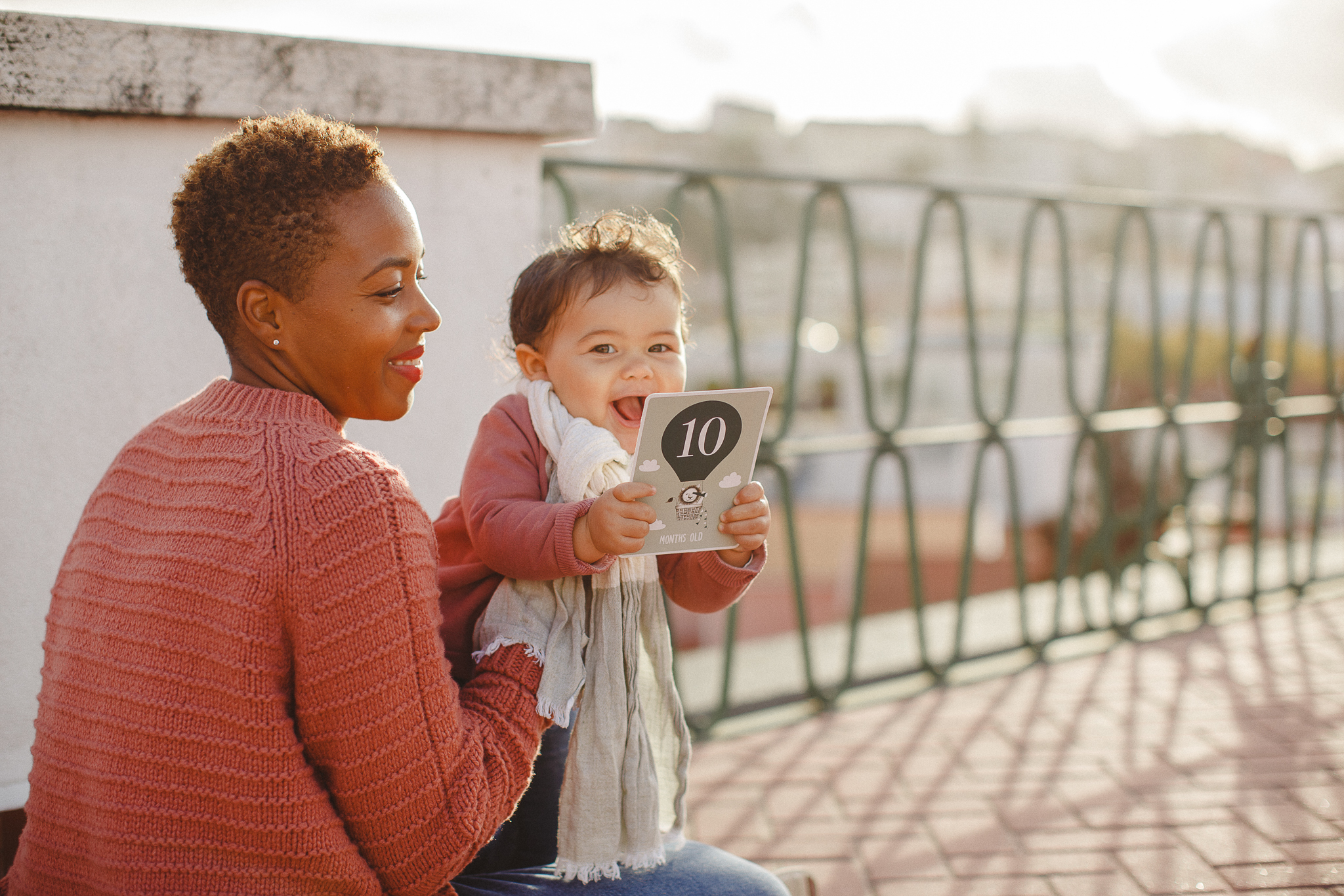Baby girl smiling holding a 10month-old sign during a family photo shoot in Lisbon with Hello Twiggs.