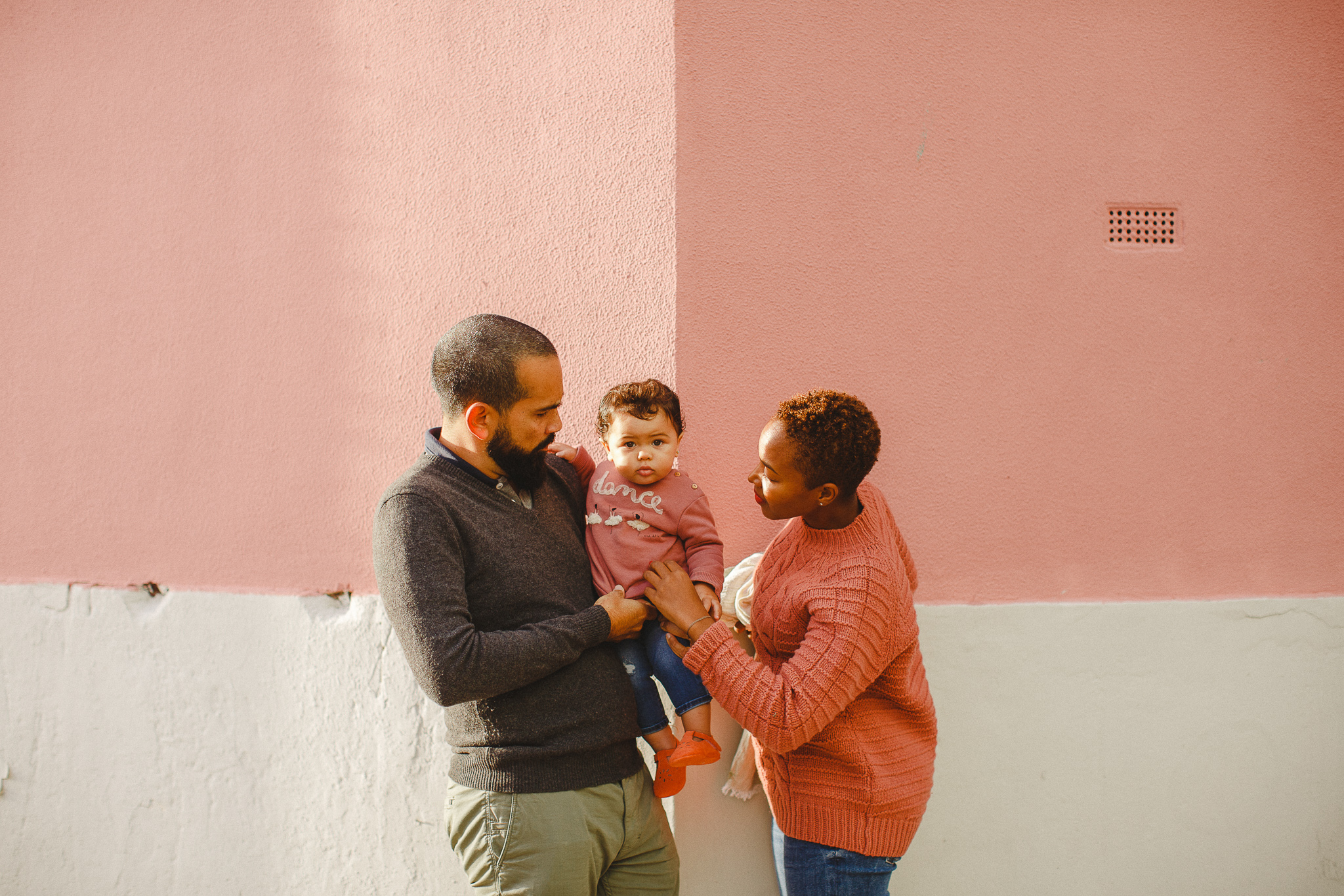 Family of three on a pink corner in Lisbon during a family photo shoot with photographer Hello Twiggs.