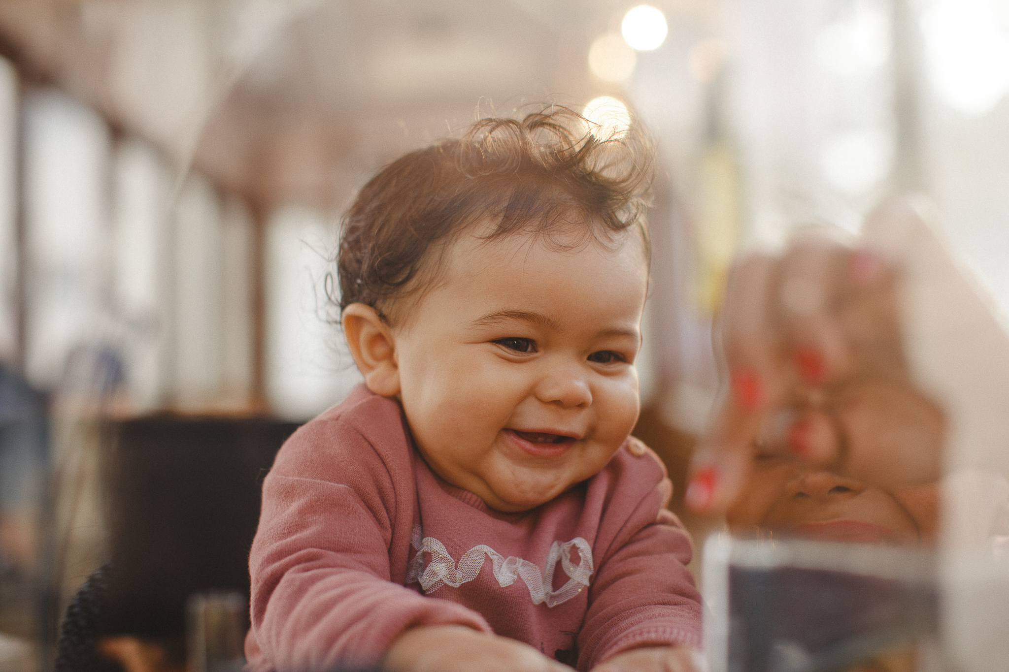Baby smiling inside of a typical yellow tram in Lisbon, during a family photo shoot.