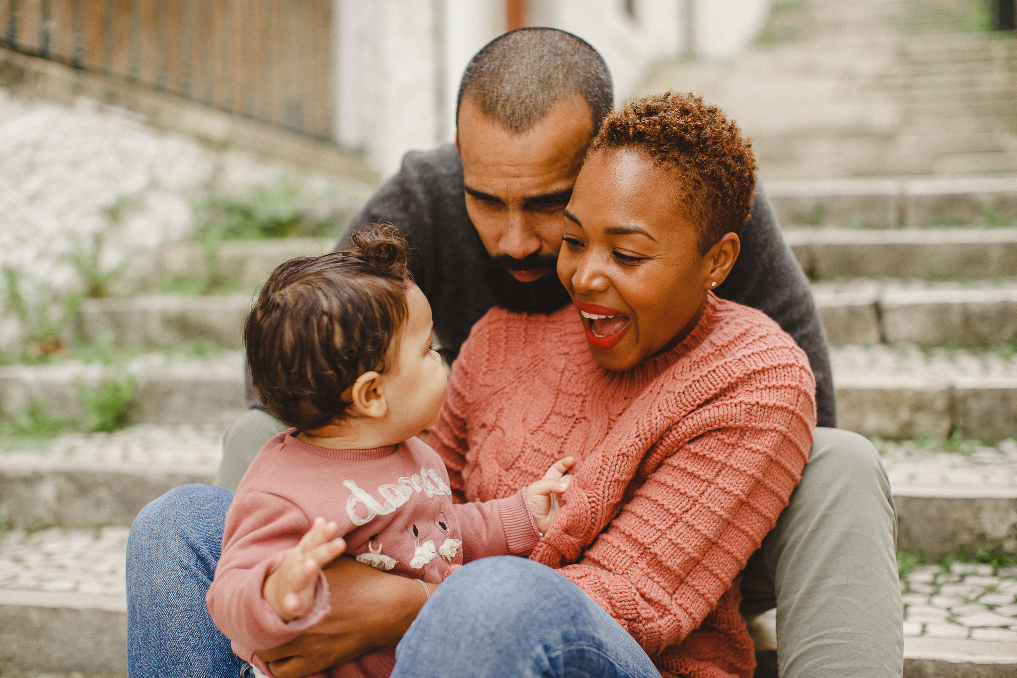 Parents smiling with baby during a family photo shoot in Lisbon.