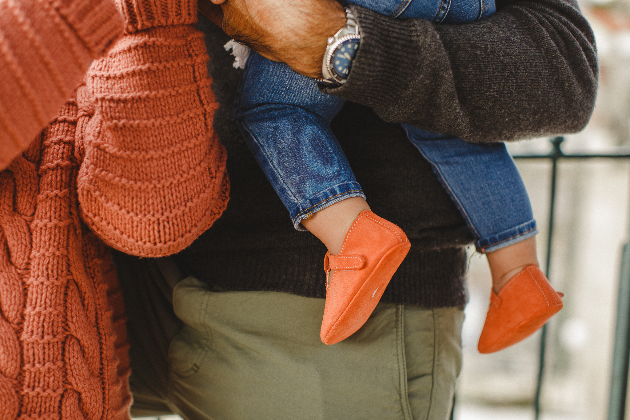 Baby being held by her dad, wearing coral's soft sole shoes.