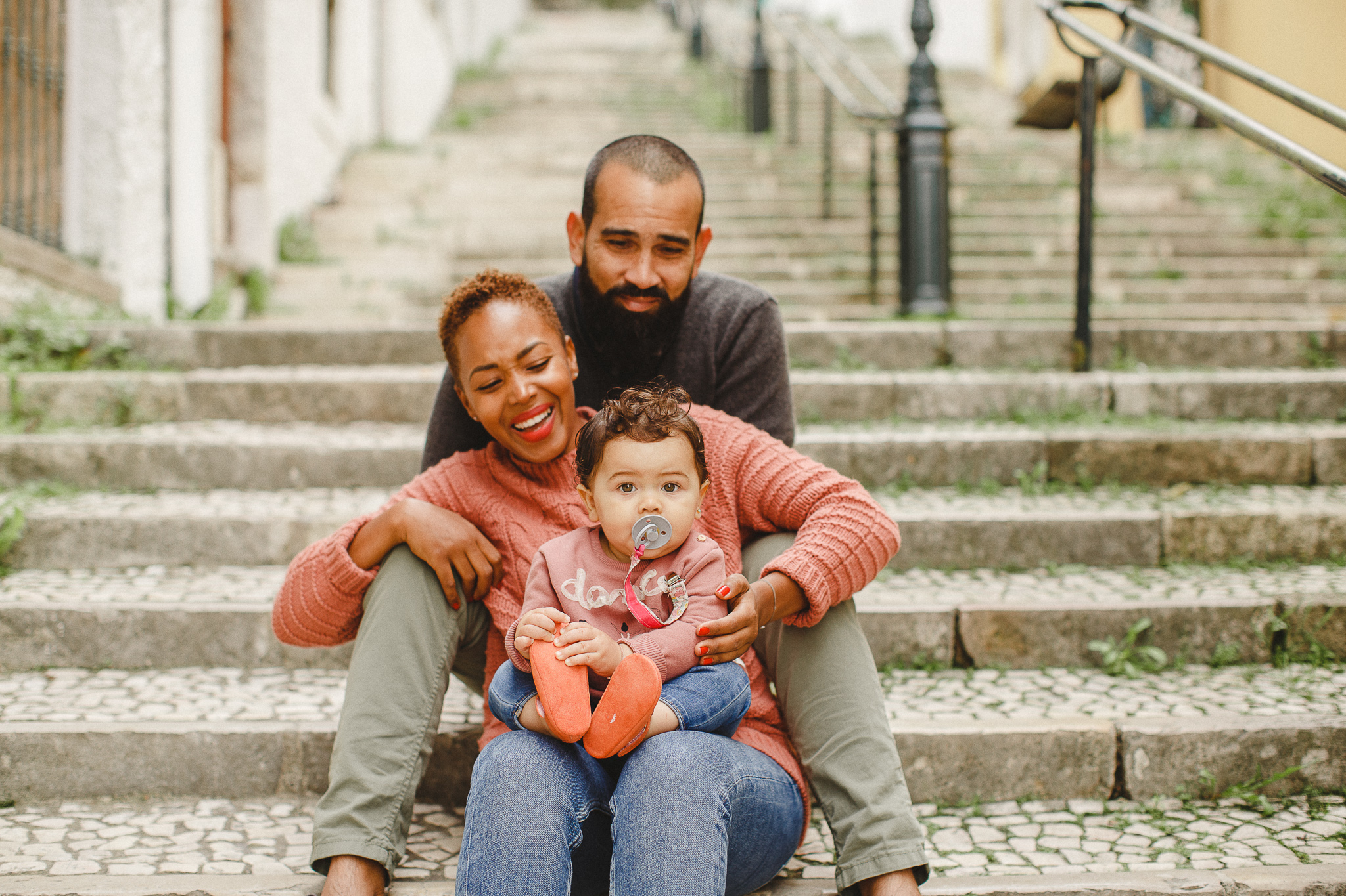 A family sitting on the stairs in Lisbon smiling during a family photo shoot.